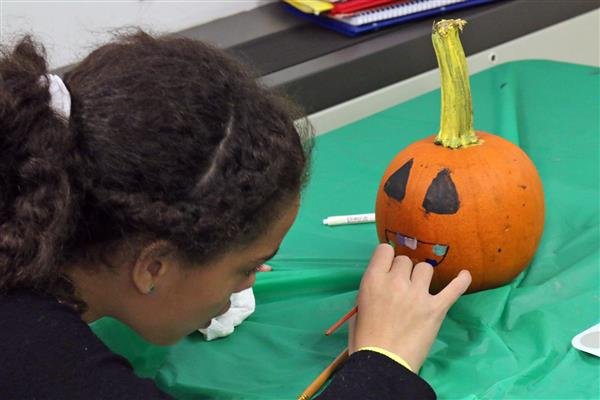 student paints a pumpkin